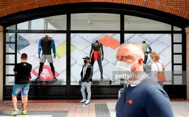 Shoppers, some wearing PPE , of a face mask or covering as a precautionary measure against COVID-19, queue to enter a recently re-opened Nike store...