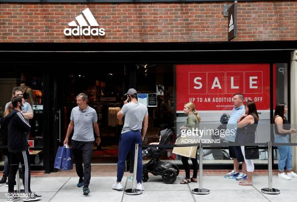 Shoppers, some wearing PPE , of a face mask or covering as a precautionary measure against COVID-19, queue to enter a recently re-opened Adidas store...