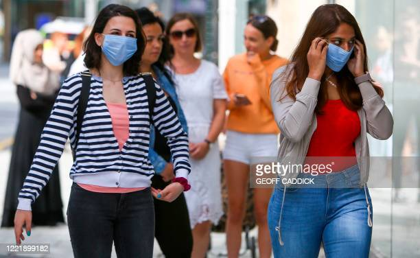 Shoppers, some wearing PPE , of a face mask or covering as a precautionary measure against spreading COVID-19, maintain the British government's...