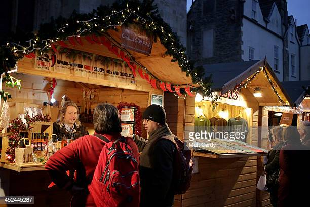 Shoppers speak with a stall holder as they browse the offerings at the Bath Christmas Market on its opening night on on November 28 2013 in Bath...