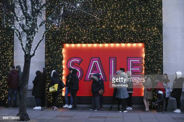 Shoppers stand in line next to a large sale sign for the Boxing Day holiday sales at the Selfridges Ltd department store in central London UK on...