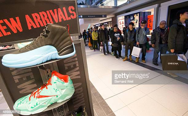 TORONTO ON DECEMBER 26 Shoppers stand in line specifically to get a pair of 'Jordan 12' running shoes for $200 per pair or the Lebran shoe below at...
