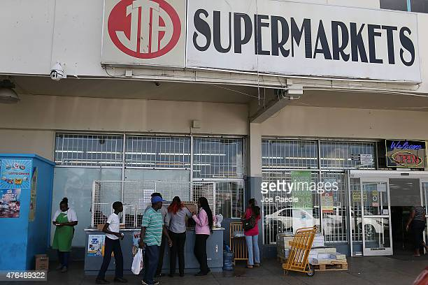 Shoppers stand outside a JTA Supermarket where former FIFA vicepresident Jack Warner is allegedly to have invested some of the FIFA money that was...