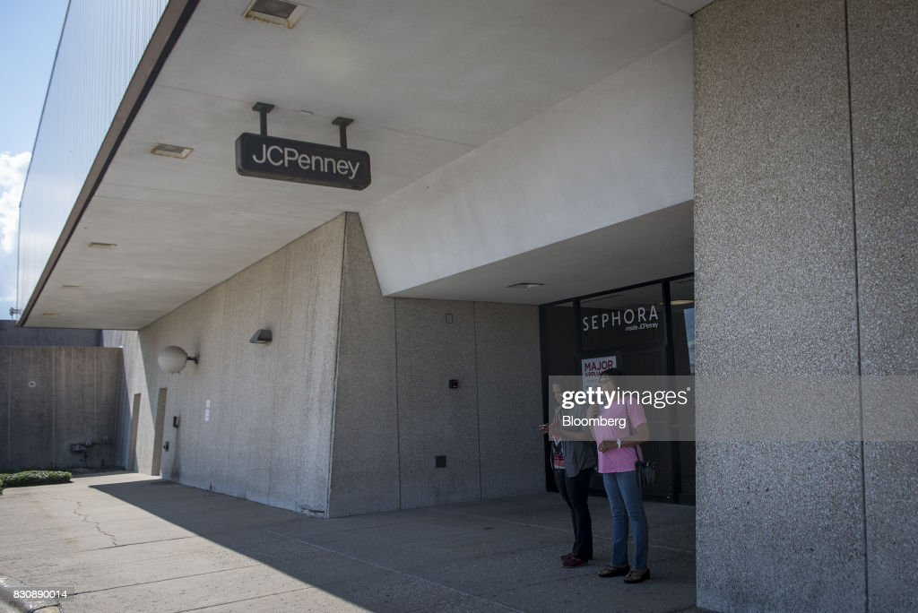 Shoppers stand outside the entrance to a JC Penney Co. store in Riverside, Illinois, U.S., on Saturday, Aug. 12, 2017. On Friday morning, JC Penney posted a deeper loss than analysts expected -- hurt by clearance sales -- sending the shares on their worst decline in more than four years. Photographer: Christopher Dilts/Bloomberg via Getty Images