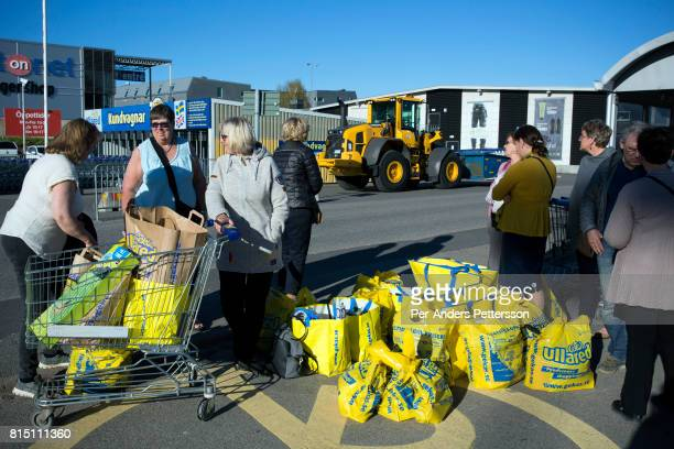 Shoppers stand with their bags on May 5 2017 in Ullared Sweden Ullared is famous for Gekas Sweden's most famous superstore founded in 1963 The shop...