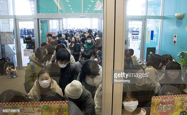 Shoppers standing behind a door wait to enter the Aeon Lake Town shopping mall operated by Aeon Retail Co a unit of Aeon Co on the first day of the...