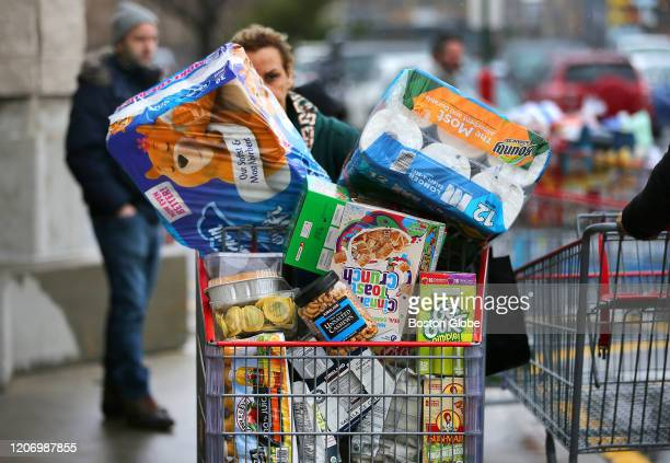 Shoppers stock up on staples including toilet paper bottled water diapers and canned goods at the Costco in Everett MA on Friday afternoon amid...