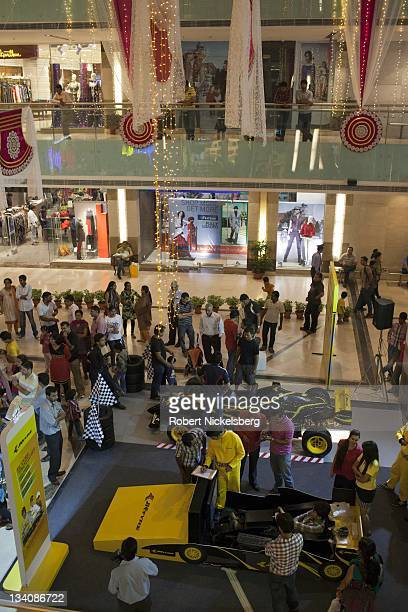 Shoppers stop at a JK Tyre racing car display October 22 2011 at the Ambience Mall in Gurgaon India On October 30 the first Indian Grand Prix took...