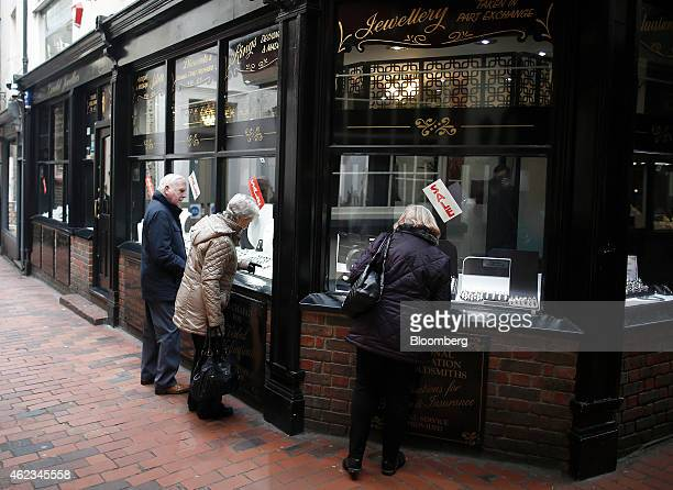Shoppers stop to look at gold and jewellery on display in the window of a jewellery store located in The Lanes at Brighton UK on Tuesday Jan 27 2015...