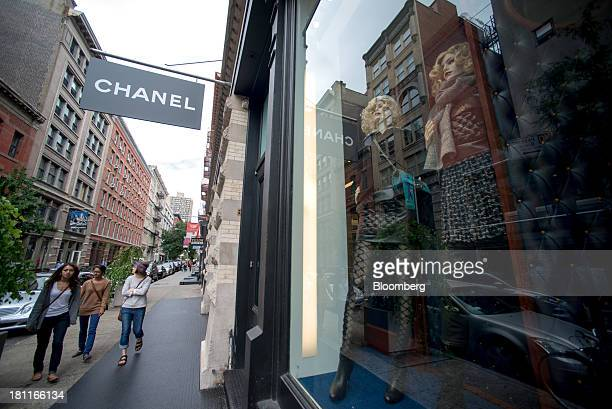 Shoppers stroll past mannequins in the window of a Chanel SA store in the shopping district of Soho in New York US on Saturday Sept 14 2013 Consumers...
