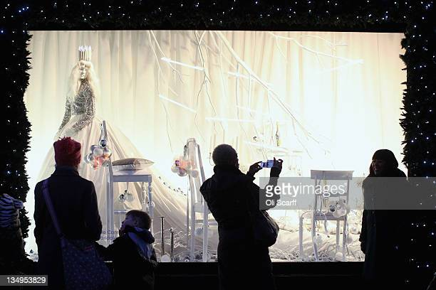 Shoppers take photographs of a window display in Selfridges department store on Oxford Street with less than three weeks before Christmas Day on...