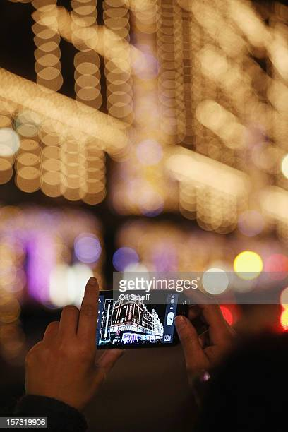 Shoppers take photographs of Harrods department store in Knightsbridge on November 29 2012 in London England Many prominent retailers in the capital...