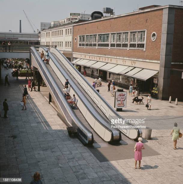 Shoppers travel down a moving walkway or travelator as they visit the Merseyway Shopping Centre, a busy shopping precinct in Stockport, near...