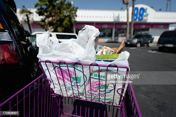Shoppers use plastic grocery bags after shopping at the 99 Cents Only Store on June 18 2013 in Los Angeles California The Los Angeles City Council is...