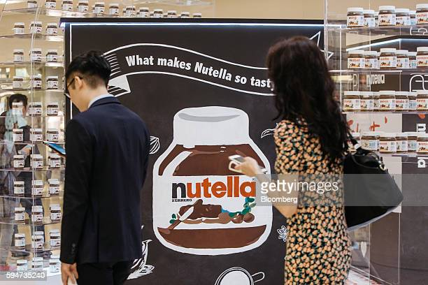 Shoppers use smartphones while standing in line at a Ferrero SpA's Nutella pop up store inside Pacific Place shopping mall in the Admiralty district...