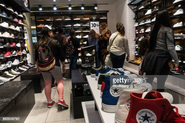 Shoppers view sneakers displayed for sale inside a store at the Plaza Reforma 222 mall in Mexico City Mexico on Monday Nov 20 2017 The National...