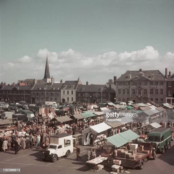Shoppers visit stalls selling produce at the farmer's market in Tuesday Market Place square in King's Lynn Norfolk England in 1954 In the background...