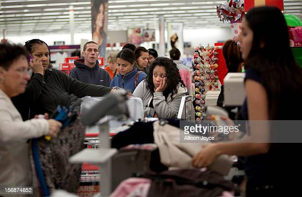Shoppers wait in a check out line at a Kmart store during the Black Friday sales on November 23 2012 in Braintree Massachusetts Black Friday the...
