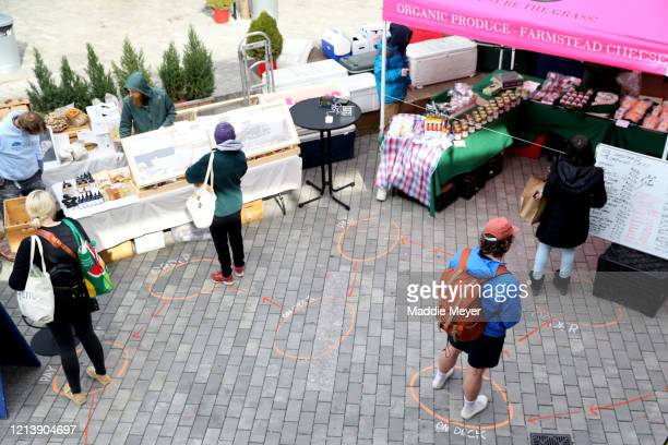 Shoppers wait in line at the Safe Supply outdoor grocery store at Bow Market on March 21 2020 in Somerville Massachusetts In order to comply with the...
