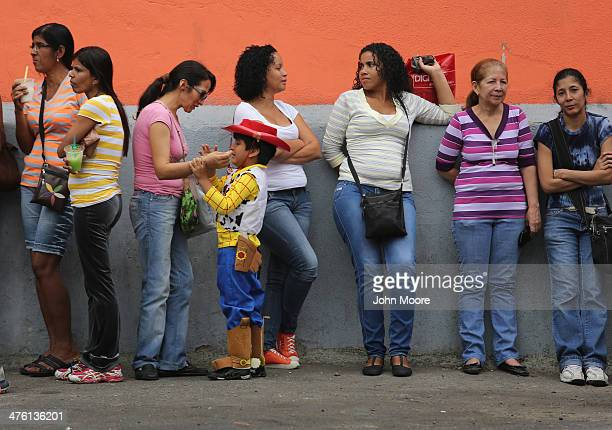 Shoppers wait in line ouside of a supermarket for scarce foodstuffs on March 2 2014 in Caracas Venezuela Venezuela has one of the highest inflation...