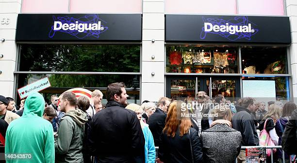 Shoppers wait in line outside a Desigual clothing store before taking part in a promotional event on June 14 2012 in Dusseldorf Germany The store as...