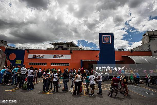 Shoppers wait in line outside a privatesector grocery store that just received a shipment of hardtofind laundry detergent in Caracas Venezuela on...