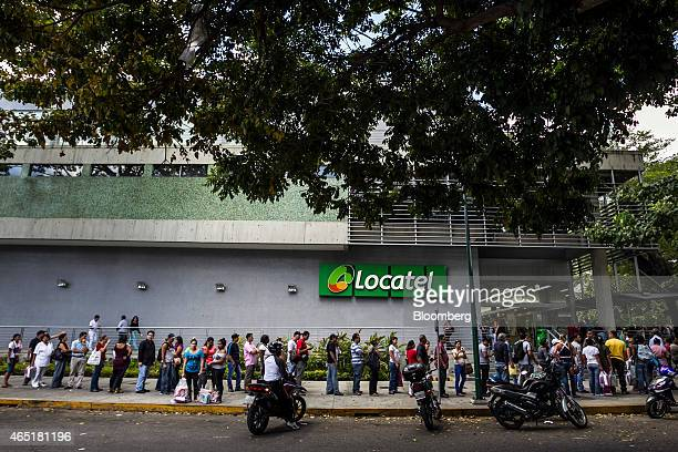 Shoppers wait in line outside of a Locatel store a privatesector pharmacy that had just received a shipment of diapers in Caracas Venezuela on...