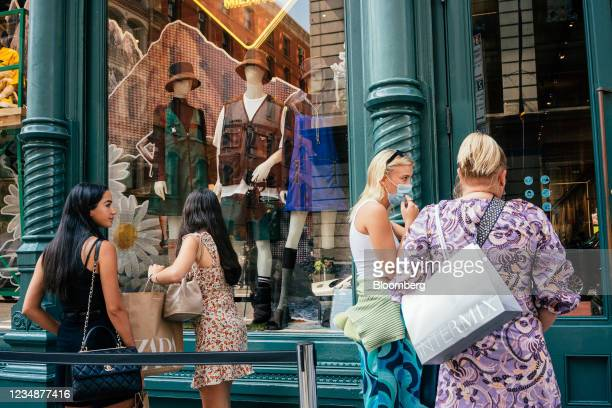 Shoppers wait in line to enter a Prada store in the SoHo neighborhood of New York, U.S., on Wednesday, Aug. 25, 2021. Consumer spending in the second...