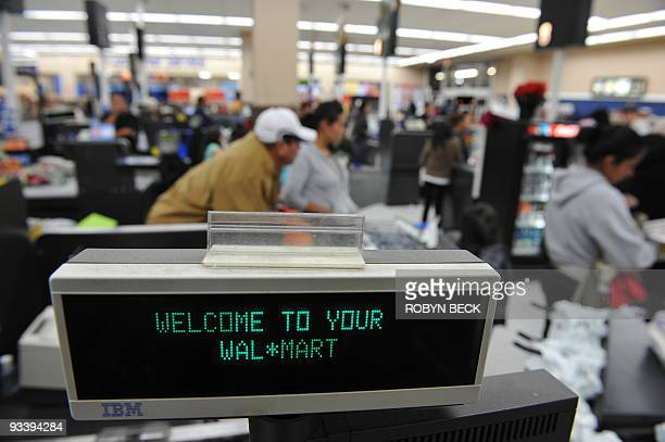 Shoppers wait in line to pay for their purchases at a Walmart store in Los Angeles California on November 24 a few days before �Black Friday� the day...