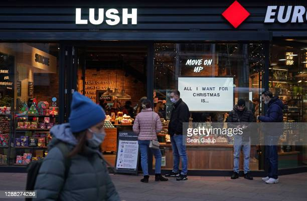 Shoppers wait to enter a Lush cosmetics store with a Christmas theme on Black Friday weekend during the second wave of the coronavirus pandemic on...