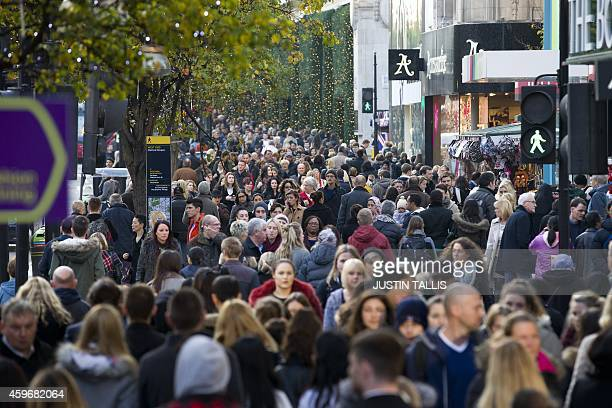 Shoppers walk along Oxford Street in central London on November 28 2014 Police blasted stores for bringing 'Black Friday' to Britain with the US...