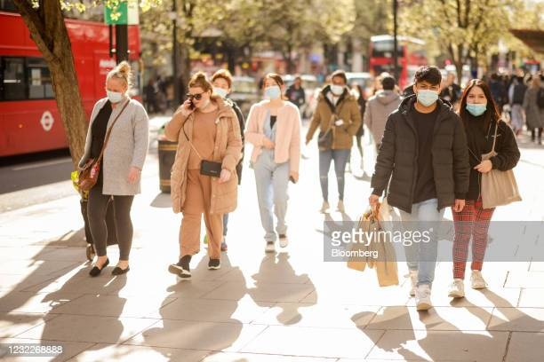 Shoppers walk along Oxford Street in central London, U.K., on Monday, April 12, 2021. Consumers flocked to shopping streets across England on Monday...