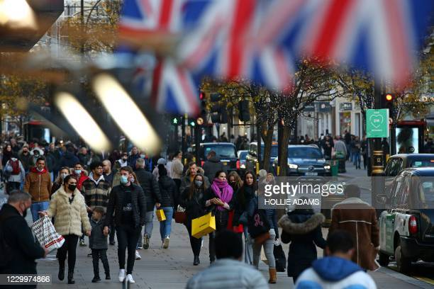 Shoppers walk along Oxford Street on the Sunday afternoon in London on December 6, 2020. - Shoppers returned to Englands high streets this week as...