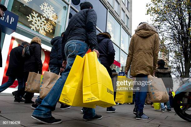 Shoppers walk along Oxford Street one of the main shopping streets in central London on December 13 2015 less than two weeks before Christmas AFP...