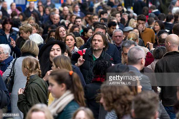 Shoppers walk along Oxford Street one of the main shopping streets in central London on December 20 on the final shopping Sunday before Christmas AFP...