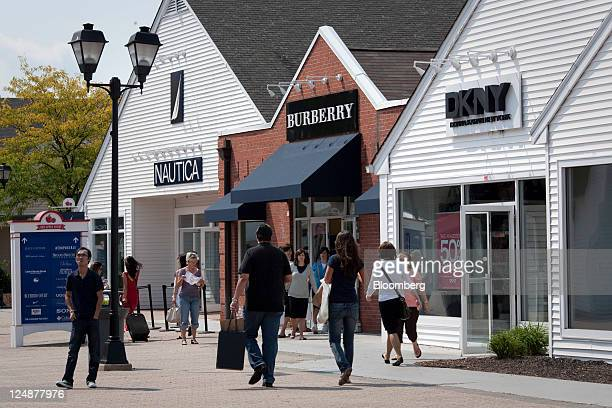 Shoppers walk along the outdoor mall at the Premium Outlets at Woodbury Common a division of Simon Property Group Inc in Central Valley New York US...