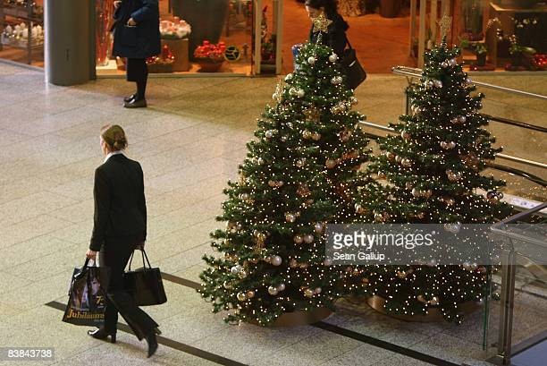 Shoppers walk among illuminated Christmas trees at the Arkaden shopping mall on November 27, 2008 in Berlin, Germany. German retailers are hoping for...