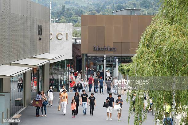 Shoppers walk at Outletcity Metzingen on August 19 2016 in Metzingen Germany Metzingen is famous for its factory outlets attracting people from all...