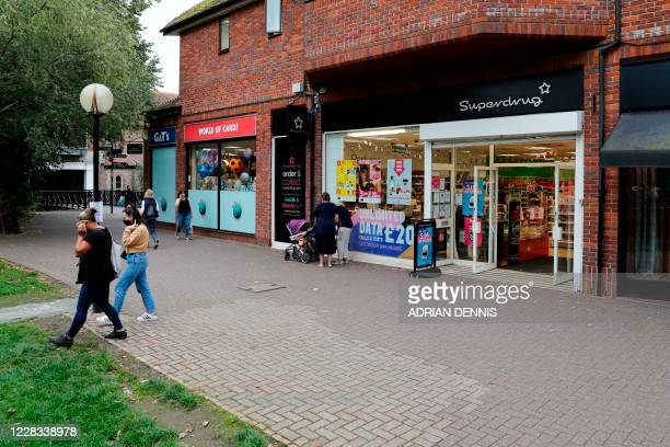 Shoppers walk by a discoloured patch of pavement in The Maltings shopping centre in Salisbury southern England on September 4 2020 where the bench...