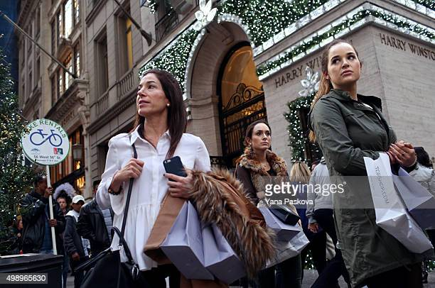 Shoppers walk by holiday decor hanging on Harry Winston in New York City on Black Friday November 27 2015 Although Black Friday sales are expected to...