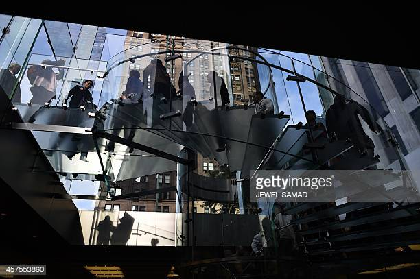 Shoppers walk down a staircase at an Apple store in New York on October 20 2014 AFP PHOTO/Jewel Samad