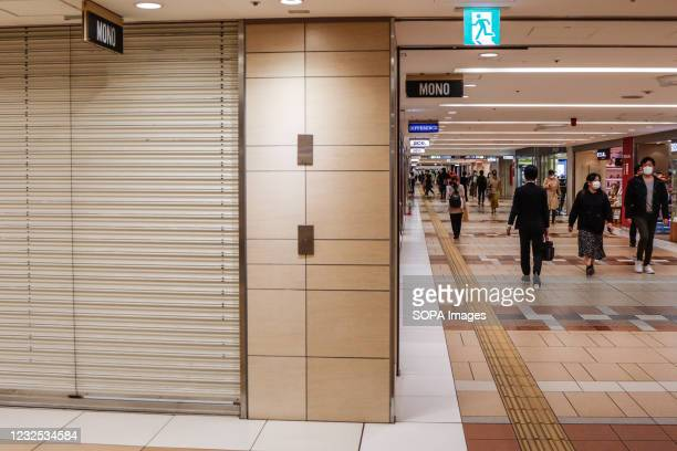 Shoppers walk in front of a large shopping center with shutters closed during a temporary holiday in Ginza. On the 25th of the first day when the...