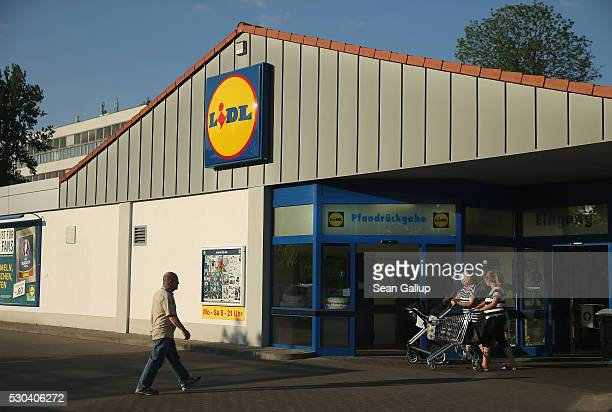Shoppers walk in front of a Lidl discount grocery store on May 10 2016 in Berlin Germany German anticartel authorities announced yesterday they are...