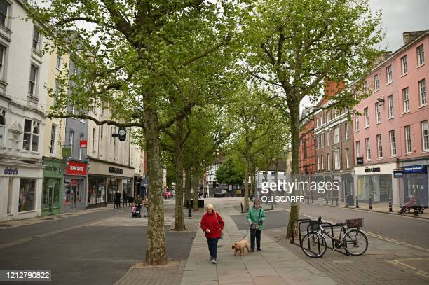 Shoppers walk in the near-deserted city centre of York, northern England on May 12 during the nationwide lockdown due to the novel coronavirus...