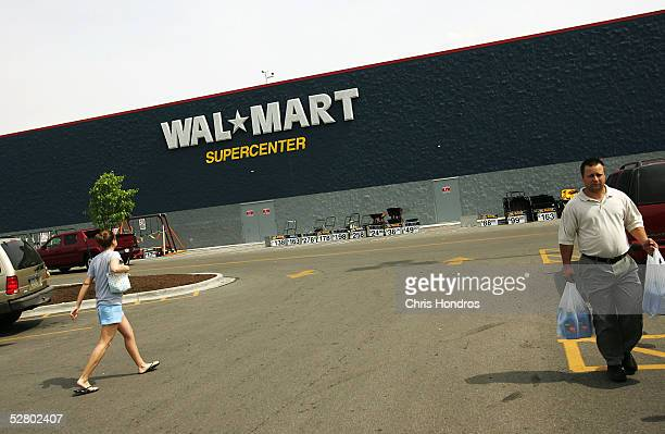 Shoppers walk in the parking lot of a WalMart Supercenter May 11 2005 in Troy Ohio WalMart America's largest retailer and the largest company in the...