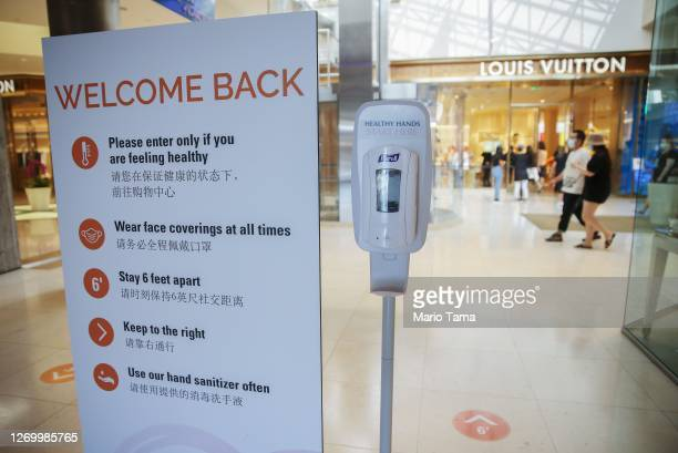 Shoppers walk near a sign posting safety guidelines in South Coast Plaza on the day it reopened after closures due to the COVID-19 pandemic on August...