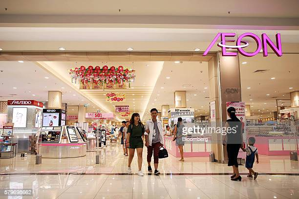 Shoppers walk near signage for Aeon Co at the retailer's mall in the Long Bien district of Hanoi Vietnam on Thursday July 21 2016 With a young...