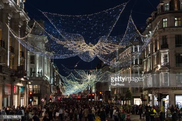 Shoppers walk on Regent Street decorated with festive lights as new coronavirus restrictions, announced today by British Prime Minister Boris...