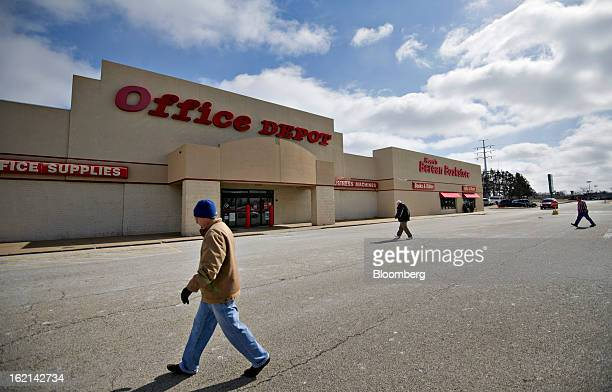 Shoppers walk outside an Office Depot Inc. Store in Peoria, Illinois, U.S., on Tuesday, Feb. 19, 2013. Office Depot Inc. And OfficeMax Inc. Are...