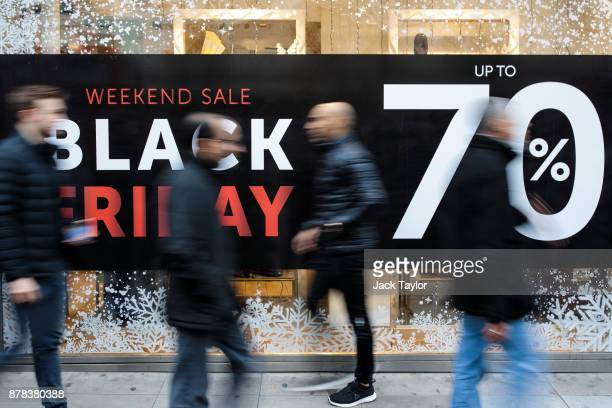 Shoppers walk past a Black Friday sale sign on Oxford Street on November 24 2017 in London England British retailers offer deals on their products as...